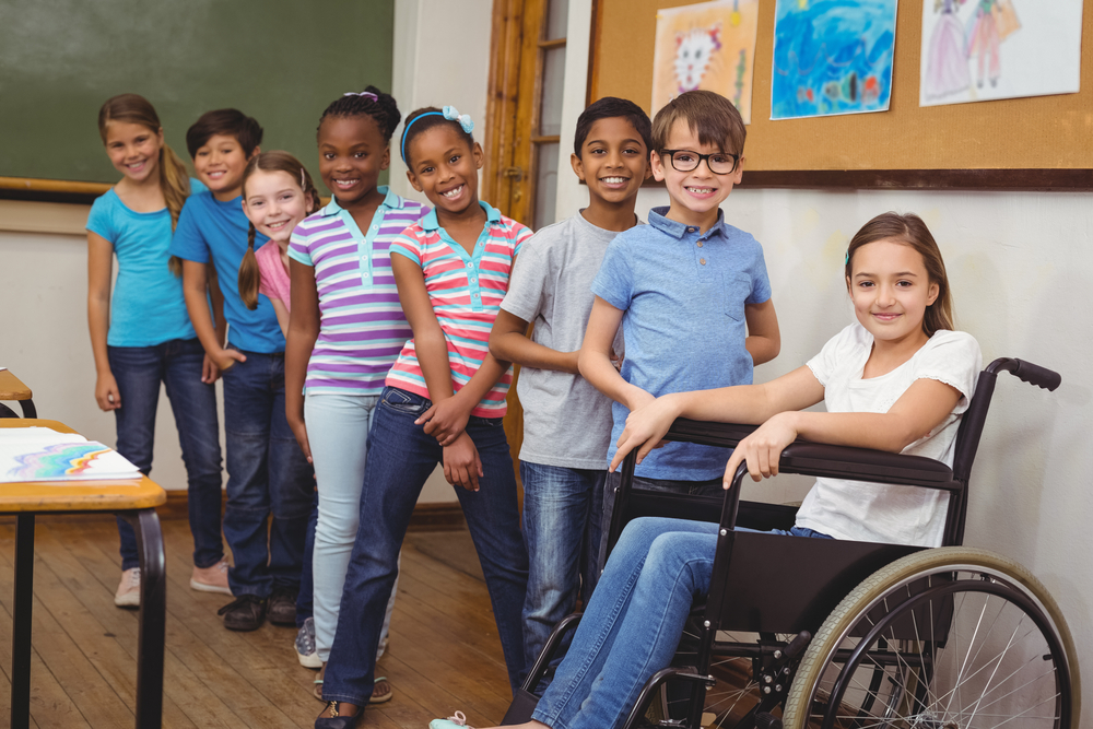 Crianças em uma sala de aula. A direita uma criança cadeirante